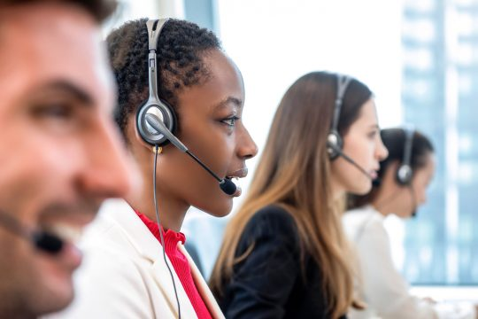 African American woman telemarketing customer service staff working with diverse team in call center office